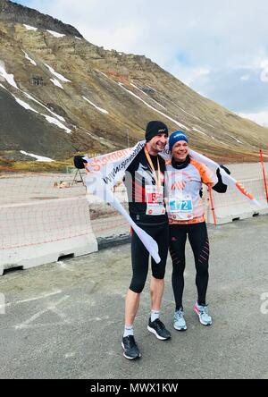 Piotr Suchenia from Poland won the Arctic Marathon in Longyearben, Svalbard Norway in a time of 2hrs, 52 minutes and 36 seconds.  the first woman was Mari Krakemo from Norway with a time of 3hrs, 3 minutes and 57 seconds just 11 seconds behind the winnner and in 4th place overall. The Svalbard Marathon is run at 78 degrees north.  Outrider with rifles and on quad bikes rode alongside the runners to protect them from polar bears. - Stock Image