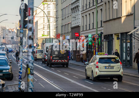 Taxi on a busy street with tram lines in Berlin, Germany - Stock Image