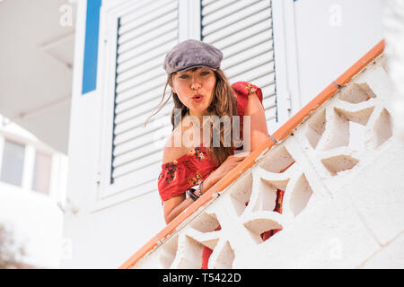 Nice beautiful trendy gitl with hat and red dress sendinkg kiss from a white balcony at home - cute people enjoying life and having fun - tourist and  - Stock Image