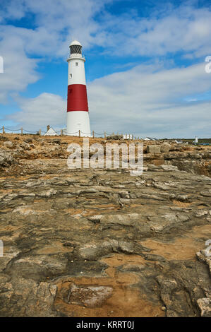 Iconic lighthouse at Portland Bill in Dorset with its wide red banding, on the cliff top. - Stock Image