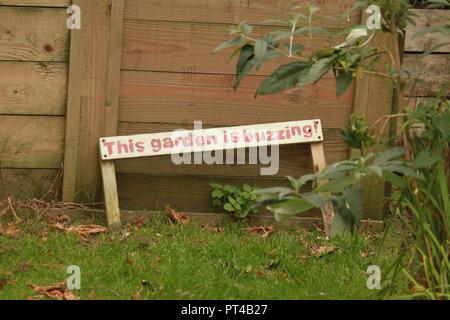 Garden wooden sign, this garden is buzzing. - Stock Image