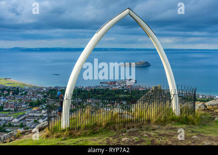 The island of Craigleith and the town of North Berwick, through replica whale bones on the summit of North Berwick Law, East Lothian, Scotland, UK - Stock Image