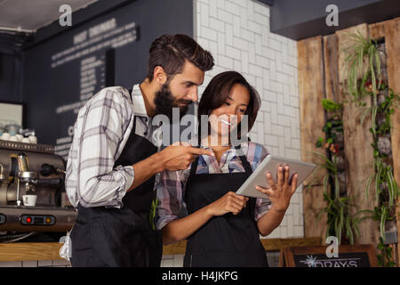 Smiling waiter and waitress interacting while using digital tablet - Stock Image