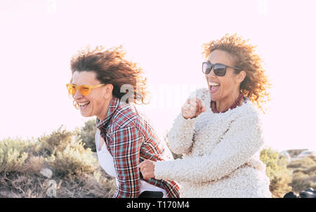 Two playful happy cheerful middle age women have lot of fun playing together - craziness and playful concept for nice people in outdoor - white sky ba - Stock Image