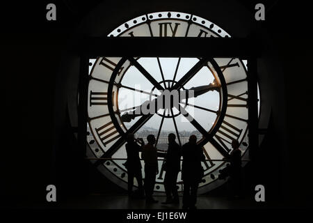 Visitors look out thought the glass clock in the Musee d'Orsay in Paris, France. - Stock Image