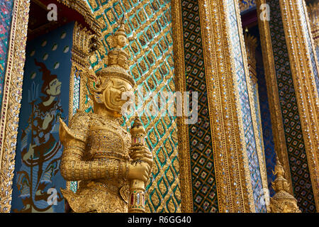 Golden Yaksha statue in the Grand Palace in Bangkok, Thailand. The demon-gods statues are a common sight in Buddhist temples in Thailand, but also fea - Stock Image
