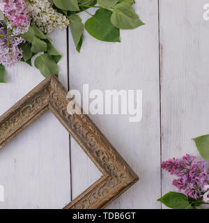 Vintage frame and decor of flowers on the background of the white-painted wooden boards. Vintage background with lilac flowers and a place under the t - Stock Image