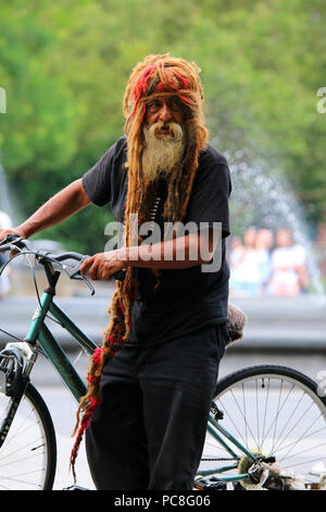 NEW YORK, NY - JULY 10: Delfine Vizearra walks a bicycle in Washington Square Park in Manhattan on JULY 10th, 2017 in New York, USA. - Stock Image