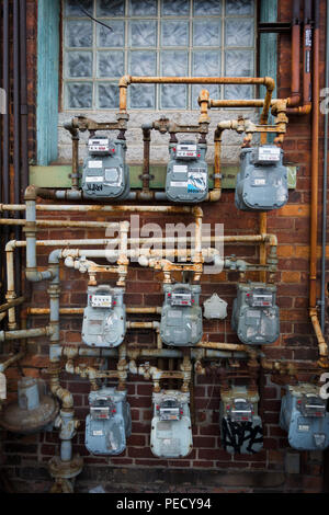A bank of natural gas meters outside of a residential apartment building. - Stock Image
