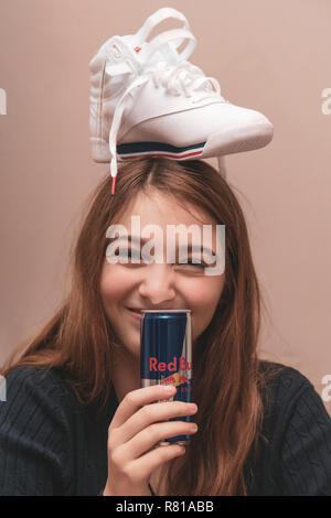 Happy female teenager celebrating turning 16 years being silly with brand new sneaker on top of head and drinking from a can of Red Bull energy drink - Stock Image