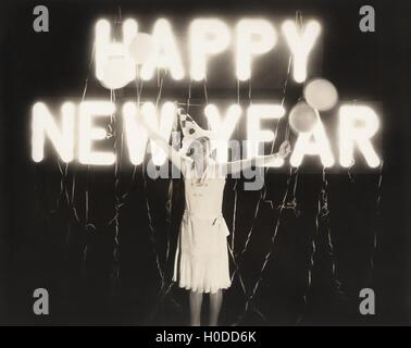 Woman standing in front of neon Happy New Year sign - Stock Image
