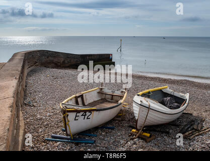 Fishing boats pulled up onto the shore beside a sea wall at Sidmouth, Devon, UK - Stock Image