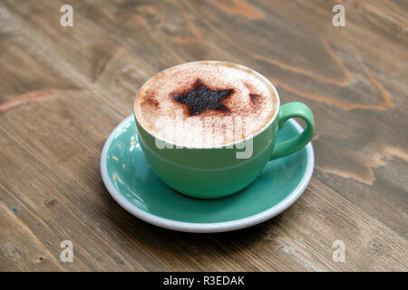 Cup of festive cappuccino coffee with a Christmas star design of chocolate sprinkled on frothy milk in a green cup and saucer in shop UK  KATHY DEWITT - Stock Image