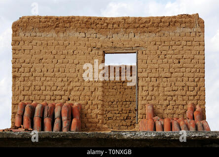 A brick wall with a hole for door. Remnants of a ruined house without a roof. Arranged tiles. - Stock Image