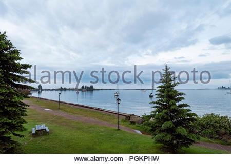 Sailboats are anchored in Grand Marais Harbor, Grand Marais, Minnesota, USA, Lake Superior in distance. - Stock Image
