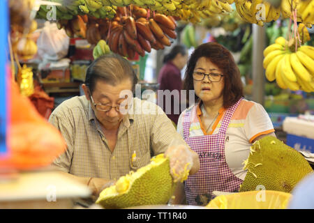 Market sellers couple in the indoor market of Little India, Singapore on a Saturday morning. - Stock Image