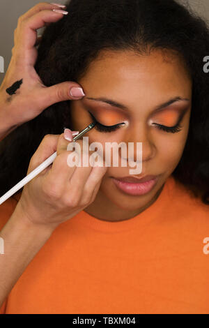 Makeup artist draws arrows on eyelids of african american girl. Evening make-up. Closeup portrait - Stock Image
