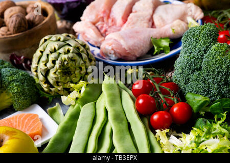 closeup of a pile of unprocessed food, such as different raw fruits and vegetables, some legumes and nuts, some pieces of chicken and fish, on a table - Stock Image