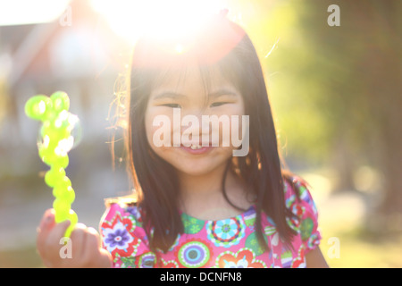Portrait of young girl at sunset with bubble wand - Stock Image