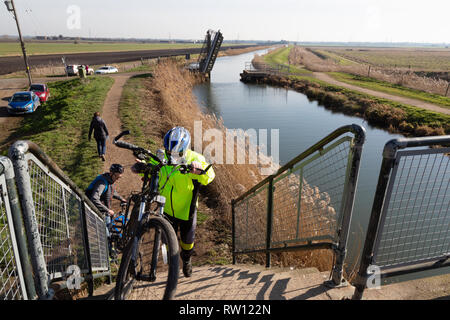 Cycling East Anglia - cyclists crossing a bridge in the fens countryside at Burwell Fen, Cambridgeshire East Anglia UK - Stock Image