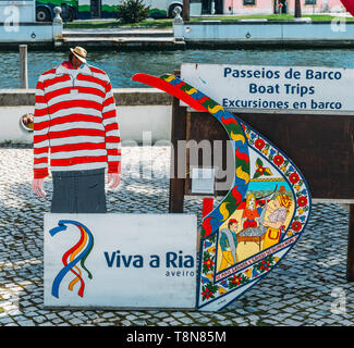 Aveiro, Portugal - April 29, 2019: Juxtaposition of facade of traditional moliceiro boat and gondolier with cut out next to a charming canal - Stock Image