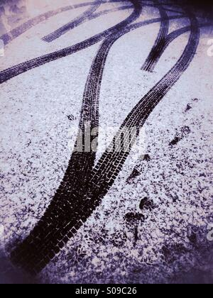 Tyre tracks forming a double heart shape on the snow covered road. - Stock Image