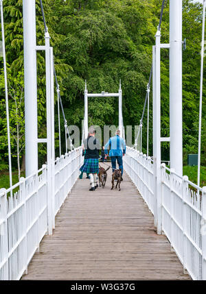 Men walking on River Ness iron footbridge to Ness Island with man wearing killt with dogs Inverness, Scotland, UK - Stock Image
