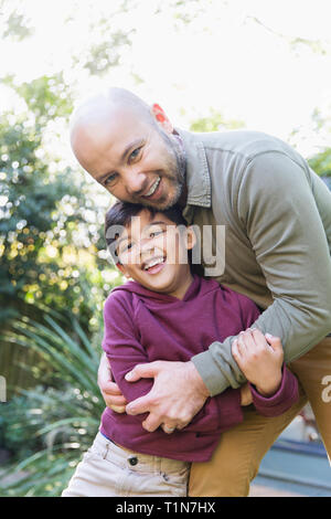 Portrait happy father and son hugging - Stock Image