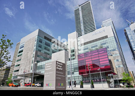 Modern facade of Women's College Hospital in Toronto on a sunny spring day with blue sky and white clouds - Stock Image