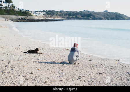 A young woman with her dog on Falmouth's Gyllyngvase Beach, Cornwall 23rd February 2016 - Stock Image