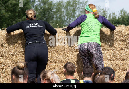 Two women climb a straw bale wall - Stock Image