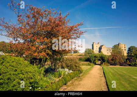 Helmsley Castle overlooking the Helmsley Walled Garden with a show of autumn flowers - Stock Image