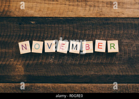 closeup of NOVEMBER alphabet tile on wooden table - Stock Image
