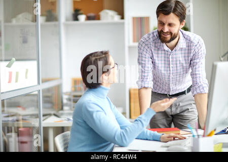 Two contemporary creative designers consulting about choice of graphics or organization moments in office - Stock Image