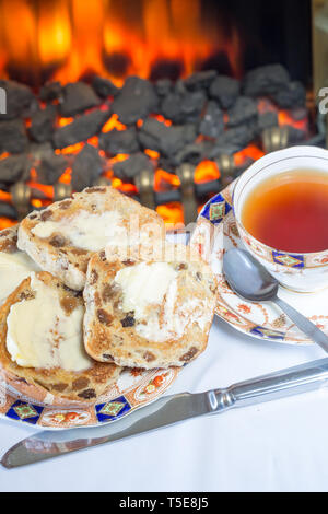 Toasted buttered Hot cross buns served for English high tea on a bone china plate with a cup of English Tea. - Stock Image