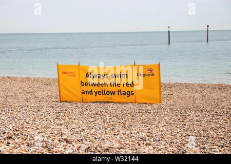 A Lifeguard sign on a pebble beach - Stock Image