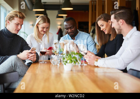 Young people with mobile phone addiction in the restaurant staring at smartphone or mobile phone - Stock Image
