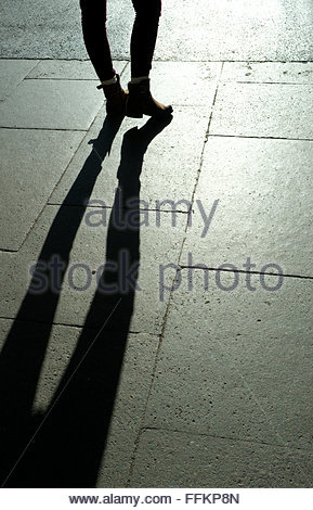 Shadow/silhouette of a young woman's legs, wearing ankle high boots, on stone paving. UK. - Stock Image