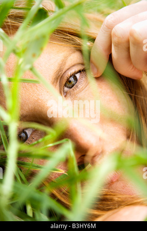 Close up portrait of pretty redhead lying in grass looking at viewer - Stock Image