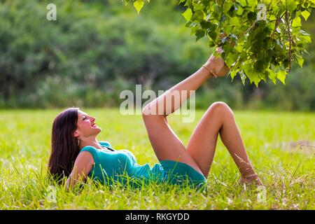 Beautiful teenager lying on greenfield in nature with legs holding in air upwards smiling  young woman legs heels - Stock Image