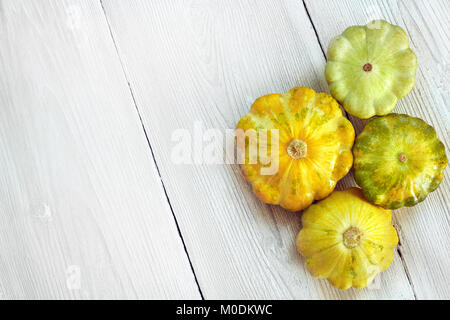 Four yellow and green bush pumpkins on white wood background. Garden,agriculture and farming concept. - Stock Image