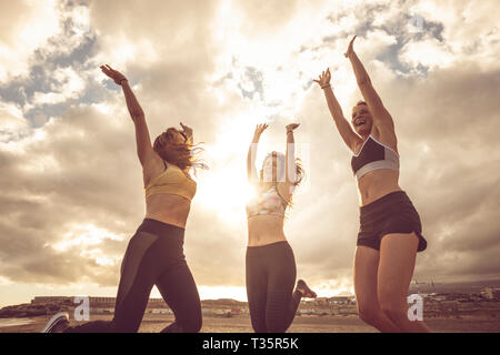 Happiness and joy for sport success active lifestyle - group of pretty females friends jumping on the air together for victory - outdoor beach sport c - Stock Image