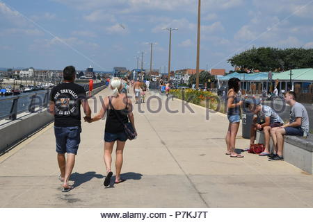 Littlehampton, UK. Saturday 7th July 2018. People stroll along the promenade on a very warm afternoon in Littlehampton, on the South Coast. Credit: Geoff Smith / Alamy Live News. - Stock Image