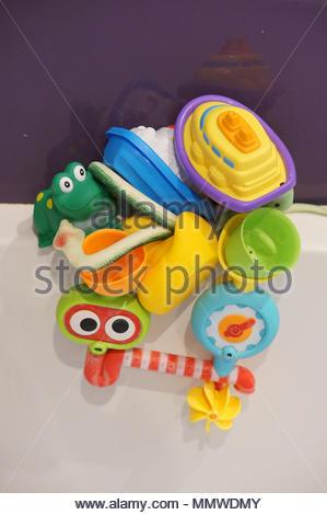 Mix of plastic bathing toys on a white bathtub - Stock Image