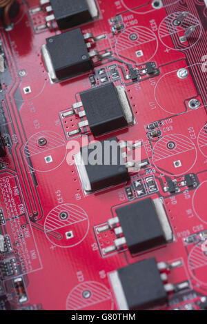 Technology concept - visual metaphor for electronics. Red circuit board / red pcb showing series of semiconductor - Stock Image