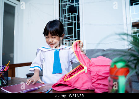 young asian kid wearing school uniform put some book in to her backpack for school - Stock Image