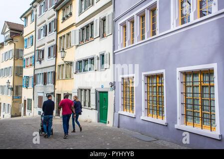Zurich, Switzerland - March 2017: Young people walking in small medieval alley street in Zurich city centre, Switzerland - Stock Image