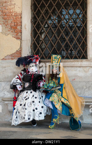 Venice, Italy. 25th Feb, 2014. Two masked and costumed performers sit outside the Doge's Palace and look at a pop up book depicting the Venice skyline. Venice Carnivale Credit:  MeonStock/Alamy Live News - Stock Image
