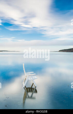 White lounge chair in sea - Stock Image