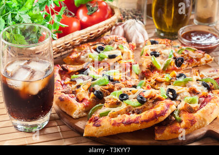 Pizza with chicken gyros, green pepper, olives and onion on cutting board. Served with cola - Stock Image